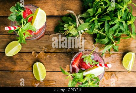 Cócteles de verano mojito de fresa con menta y limón en vidrios