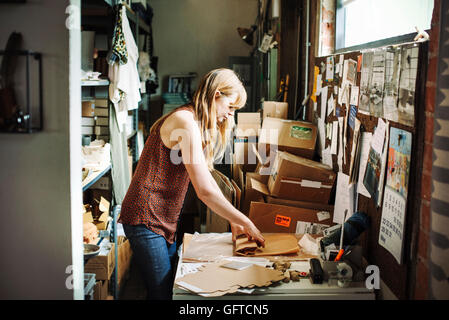 Mujer con largo cabello rubio de pie en el almacén de una tienda de mercancía en envoltura de papel marrón