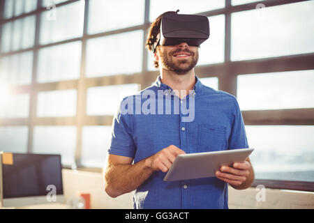 Ejecutivo de negocios masculinos en casco de realidad virtual mediante tableta digital