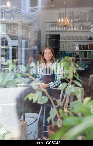 Retrato de una mujer alegre y situándose en flower shop