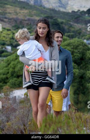 Feliz familia joven caminando sobre hierba paisaje Foto de stock