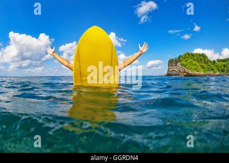 Joven surfista feliz chica con propagación de manos sentarse sobre surf board y se divierte. Estilo de vida saludable, la gente, el agua enseñanzas deportivas.
