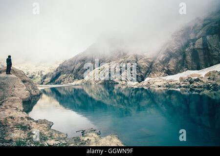 Hombre de pie solo viajero en Cliff lago y montañas brumosas sobre antecedentes en el estilo de vida al aire libre Foto de stock