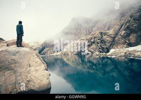 Hombre de pie solo viajero acantilado de piedra sobre el lago y las montañas nubladas sobre antecedentes de viajes al aire libre Concepto de estilo de vida