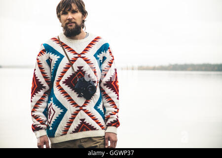Joven barbudo con cámara de fotos de viaje Moda retro Lifestyle vistiendo ropa suéter tejido exterior de carácter nebuloso en la espalda