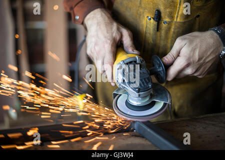 Trabajador de mobiliario personalizado muele la junta de soldadura en el bastidor de acero. Foto de stock