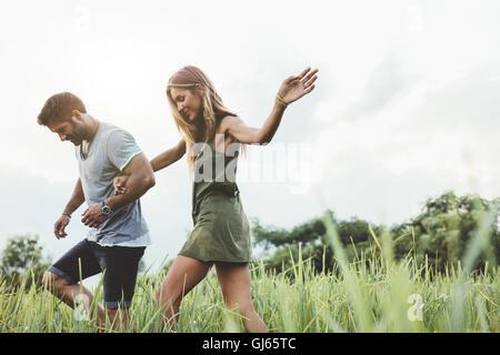 Disparó al aire libre de la joven pareja caminando por los prados de la mano. Hombre y mujer hablando a pie a través de campo de hierba en el campo.