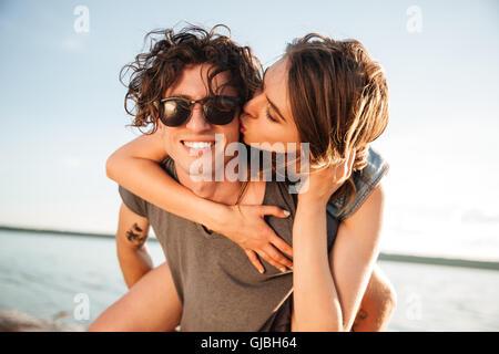Joven dando piggyback ride a la novia por el océano