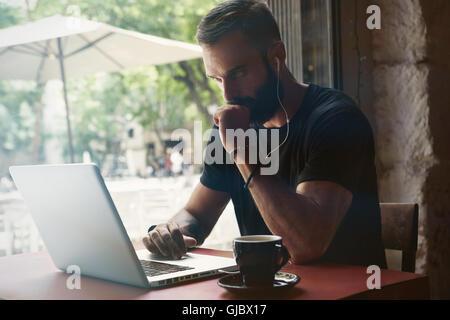 Empresario joven barbudo concentrada vistiendo negro Tshirt Trabajo Urbano portátil Cafe.hombre sentado Tabla de madera taza de café mirando a través de la ventana.Coworking proceso Business Startup.fondo borroso