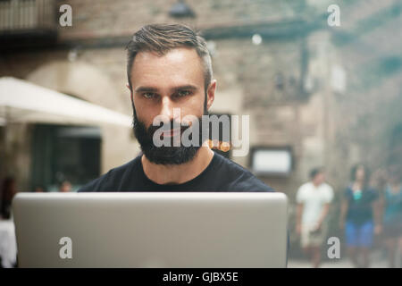 Closeup retrato guapo empresario barbudo vistiendo negro Tshirt Trabajo Urbano portátil Cafe.Joven Manager portátil de trabajo exterior.Coworking proceso Business Startup.fondo difuminado.