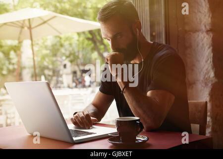 Empresario joven barbudo concentrada vistiendo negro Tshirt Trabajo Urbano portátil Cafe.hombre sentado Tabla Taza Café escuchando música.Coworking proceso Business Startup.fondo borroso.Filtro de color.