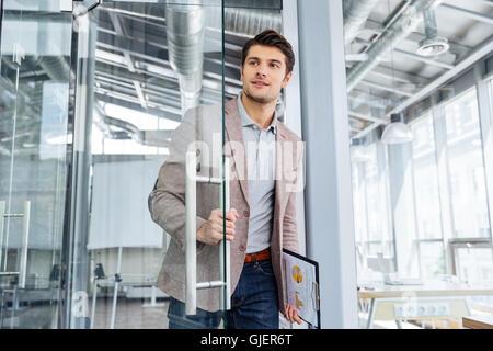 Apuesto joven empresario con portapapeles entrando en la puerta de oficina Foto de stock