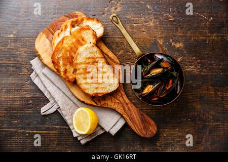 Mejillones en olla de cobre, tostadas de pan y limón sobre fondo de madera