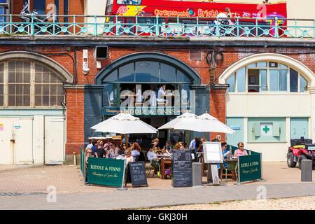 Riddle & finlandeses, frente al mar que ofrece un bar de ostras y champán en Brighton, East Sussex, Reino Unido en un día soleado de verano