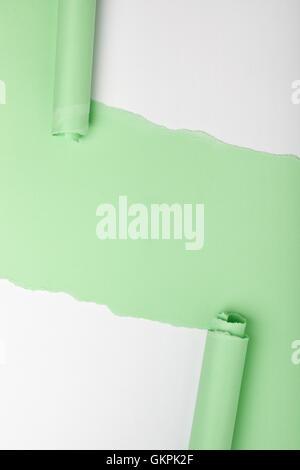 Las lágrimas en un pedazo de papel verde revelando fondo blanco debajo