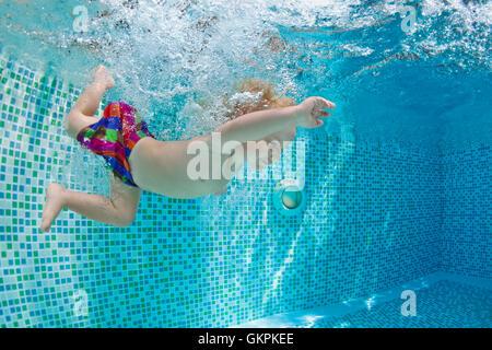 Gracioso foto del bebé activo natación, buceo en piscina con diversión, salto hacia abajo subacuático con salpicaduras y espuma. Estilo de vida familiar