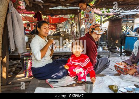 Alegre familia de expositores con un lindo joven vistiendo thanaka, Mercado de Jade, Mandalay, Myanmar (Birmania)