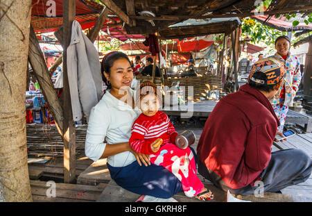 Familia Stallholder con un lindo joven vistiendo thanaka, Mercado de Jade, Mandalay, Myanmar (Birmania)