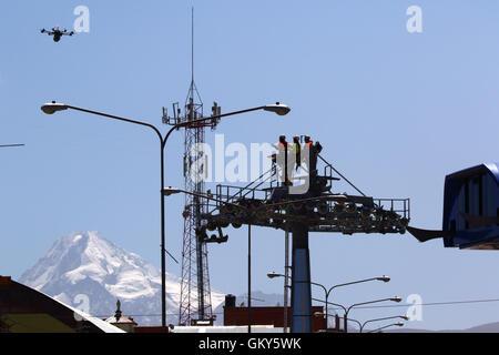 El Alto, Bolivia, 23 de agosto de 2016.Tecnicos espere un zumbido que está llevando un cable sintético liviano entre los pilones de un nuevo telecabina / telecabina que está bajo construcción. Esta es la primera parte del proceso para instalar el cable de acero definitivo que llevará las góndolas. Este teleférico entre el Río Seco y la ceja en El Alto es uno de una segunda fase de líneas de tranvía que forman parte de un ambicioso proyecto para aliviar la congestión del tráfico. 3 rutas desde la primera fase ya funcionan entre las ciudades de La Paz y El Alto. Mt Huayna Potosí es en el fondo.