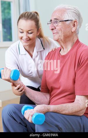 Trabajar con varones Senior fisioterapeuta utilizando Pesos