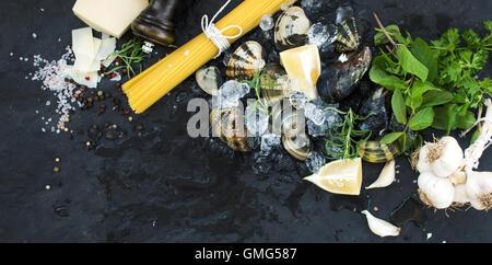 Ingredientes para cocinar Spaghetti vongole. Almejas de hielo rotos, pasta cruda, queso parmesano, ajo, perejil y limón sobre piedra pizarra antecedentes, vista superior