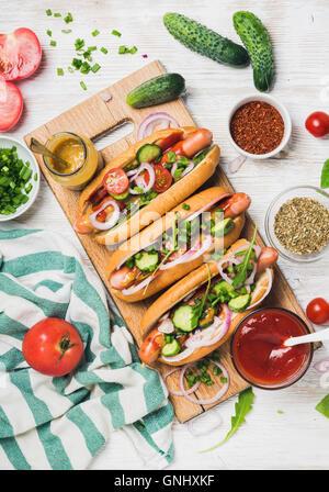 Perritos calientes caseros en madera sirviendo a bordo con verduras frescas, las especias, la salsa de tomate y la mostaza sobre fondo pintado de blanco, top