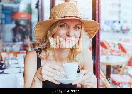 Retrato de moda bella mujer de mediana edad en el café con una taza de café, alegre, sonriente y mirando la cámara