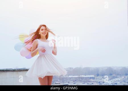Feliz verano joven con globos de colores Foto de stock