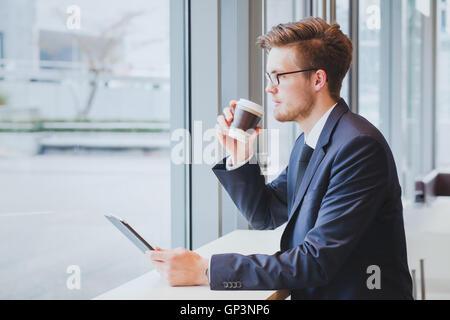 Hombre de negocios pensando, bebiendo café y mirando a la ventana en la moderna cafetería interior Foto de stock
