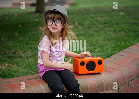 Escucha música en hipster chica retro busca altavoz inalámbrico Foto de stock