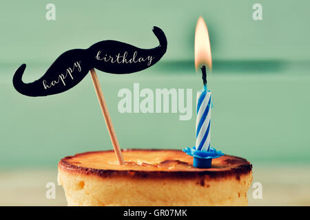 Primer plano de un cheesecake rematado con un bigote con el texto escrito en él feliz cumpleaños y acoplado a un palo y un encendido bi