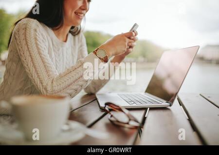 Captura recortada del joven a través de teléfono móvil en la cafetería al aire libre. Mujer sentada en la mesa con el portátil en su mensaje de texto de lectura