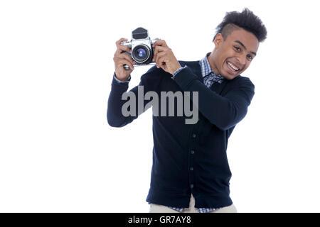 Africano joven hombre sujetando una vieja cámara y ser feliz en las fotos tomadas.
