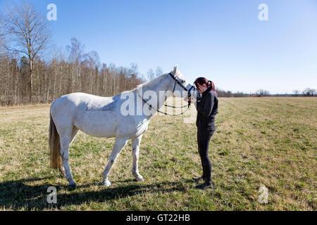 Mujer besando a caballo en campo durante el día soleado Foto de stock