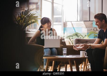 Tiro de dos socios de negocios sentada en el vestíbulo de la oficina y sonriendo. Mujer con un portátil discutir ideas de negocio con machos colleag