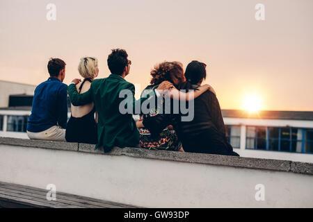 Vista trasera de hombres y mujeres jóvenes relajándose juntos en la azotea y mirar el atardecer. Amigos multirracial sentado en la terraza en e