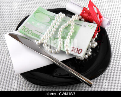 Dinero en placa, cuchillo, diamantes y arco de regalo en papel blanco Foto de stock
