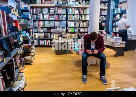 Copenhague, Dinamarca, en el interior, el Museo Nacional Nationalmuseet, Teen mirando Smart Phone en Bookstore