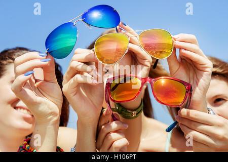 Tres jóvenes amigas con gafas de sol de manos Foto de stock