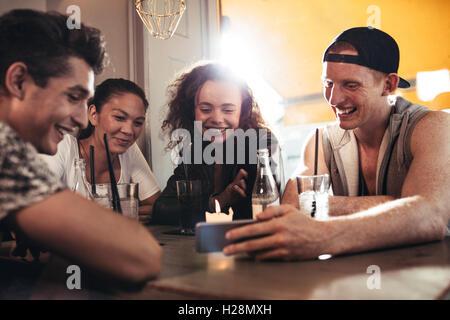 Alegres jóvenes amigos mirando teléfono inteligente mientras está sentado en la cafetería. Mestizos sentado en una mesa en el restaurante con mo