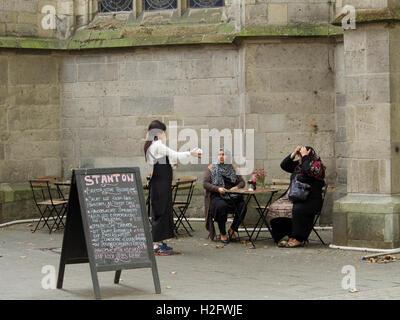 Dos mujeres musulmanas en una mesa de café al aire libre en el centro de la ciudad de Colonia, Alemania Foto de stock