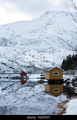 Cabañas por un lago reflectantes, las islas Lofoten, Noruega