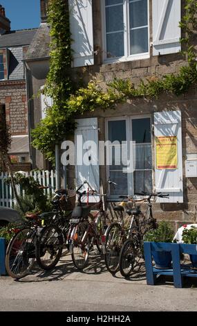 La comuna costera de Barfleur en Normandía, noroeste de Francia. Ciclos turísticos estacionados fuera de una casa de granito con persianas
