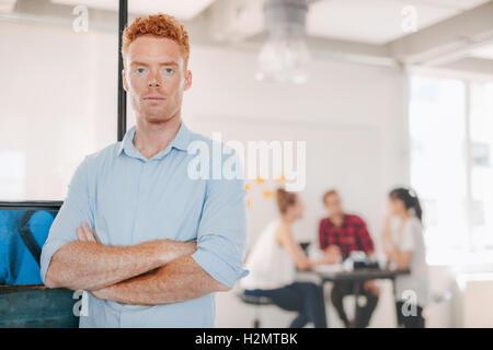 Retrato del joven empresario confía en la oficina permanente con sus brazos cruzados y sus colegas reunidos en segundo plano.