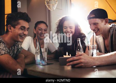 Grupo de Amigos sentados juntos en un café mirando al teléfono móvil y sonriente. Joven mostrando algo a sus amigos en h