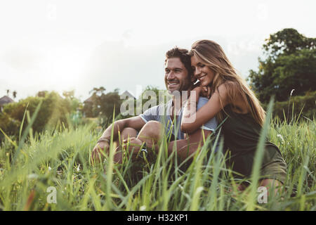 Disparó al aire libre de jóvenes amantes felices sentados en el prado. Feliz pareja joven en la hierba. Foto de stock