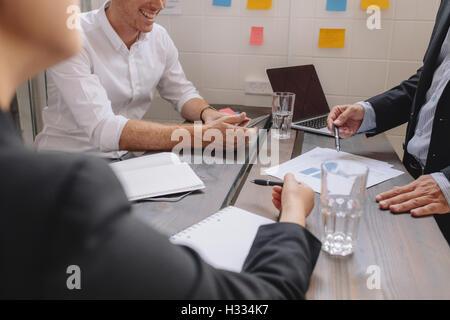 Cerca del empresario explicando un plan financiero a sus colegas en la reunión. Gente de negocios discutir un plan financiero alrededor