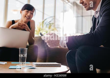 El hombre de negocios joven a través de teléfono móvil con una mujer sentada en el fondo. Los empresarios reunidos en el vestíbulo de oficina.