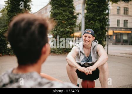 Sonriente joven sentada sobre baloncesto y hablando con un amigo. Dos amigos relajante después de un partido de baloncesto en la cancha.
