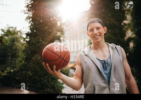Retrato del joven sonriente sosteniendo una pelota de baloncesto en el tribunal exterior. Chico adolescente mirando a la cámara con una bola en la mano.